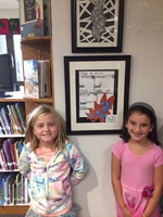 Cultural arts helpers hang student art work