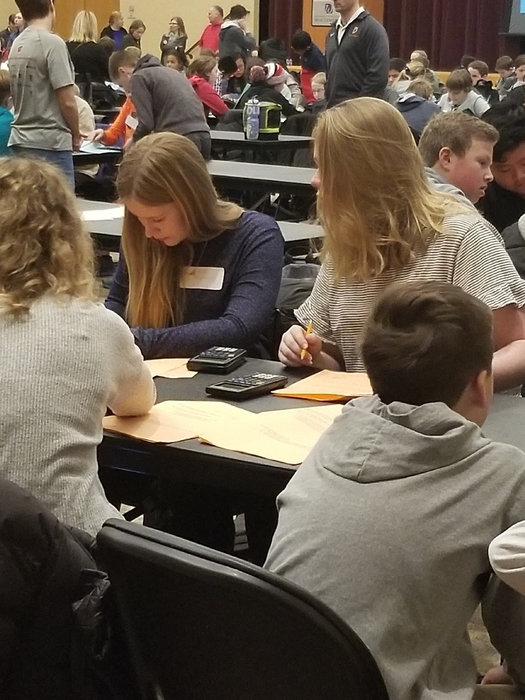 Grace Hanson fills in the final answer sheet after the team finishes.