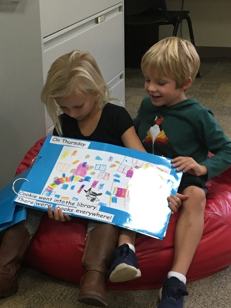 Two first graders reading their book